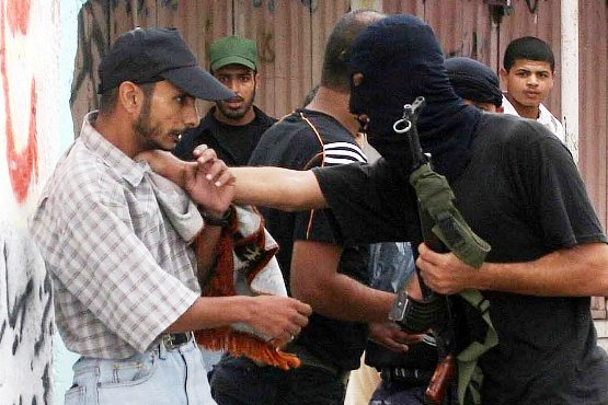 Members of Hamas forces arrest a Fatah party supporter